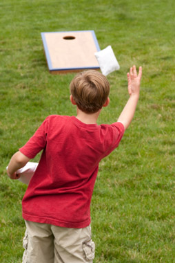 Boy playing cornhole